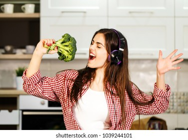 Lovely long-haired girl having fun as cooking, wearing casual blue jeans and checked red shirt, singing in headphones, indoor shot in huge white kitchen