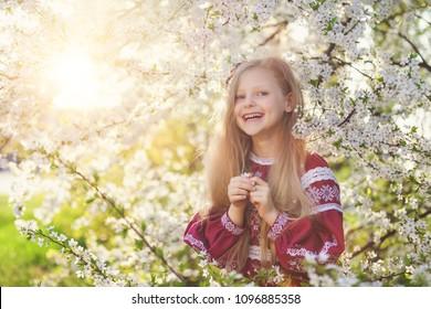 Lovely lttle girl stands under a blooming plum in park in ethnic ukrainian dress