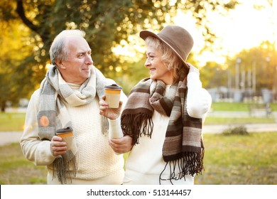Lovely mature couple with coffee in autumn park