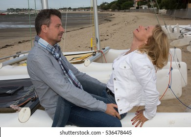 lovely mature couple in love during vacation on sand beach near boat
