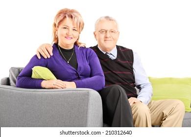 Lovely mature couple sitting on sofa isolated on white background