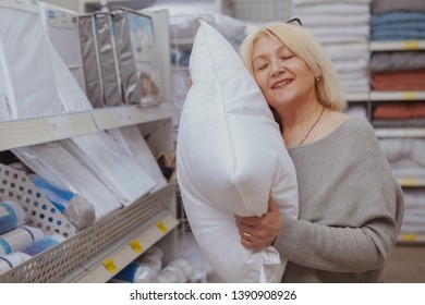 Lovely mature woman smiling with her eyes closed, trying soft pillow at furnishings store. Happy female customer smiling in pleasure, shopping for pillows and cushions for her apartment