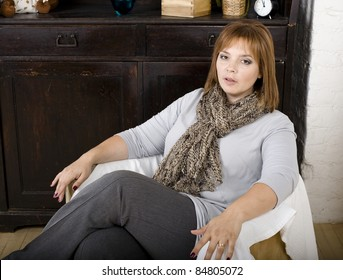 A lovely middle aged woman smiling while sitting at home