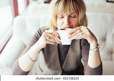 Lovely middle-aged blond woman with a beaming smile sitting in cafe having coffee