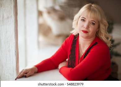 Lovely middle-aged blond woman with a beaming smile at home looking at the camera