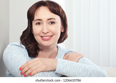 Lovely middle-aged brunette woman with a beaming smile sitting on sofa at home looking at the camera