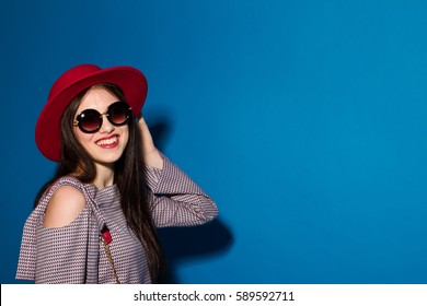 Lovely model in fashionable red Hat and a red Clutch on blue background.