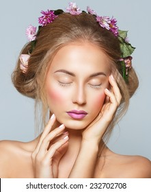 Lovely model with shiny volume curly hair with flowers, winter white eyelashes make-up, vivid lips and pink cheeks. Christmas look