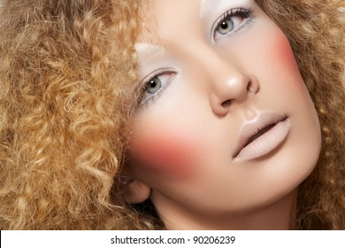 Lovely model with shiny volume curly hair, winter white eyeshadows make-up, pale lips and pink cheeks. Christmas look with frizzy hairstyle