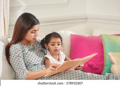 Lovely moment of maternity: middle-aged mother sitting on sofa with her cute little daughter and reading fairy-tales to her