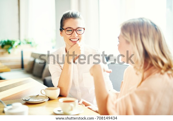 Lovely moments of friendship: cheerful young women gathered together at cozy small cafe and chatting animatedly with each other