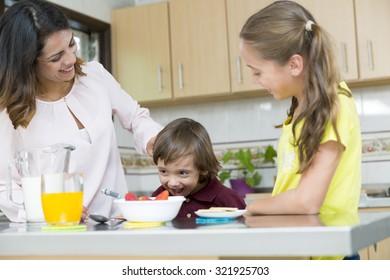 Lovely Mother and her children having breakfast in kitchen
