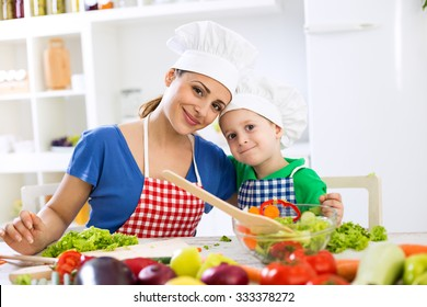 Lovely mother and kid two chefs in the kitchen at home