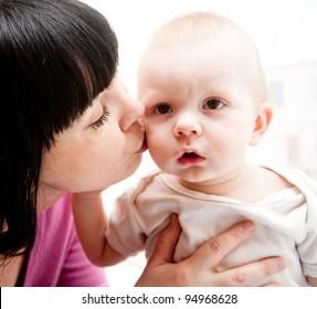 Lovely mother kissing her son - family portraits