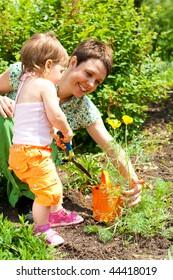 Lovely mother and toddler girl gardening