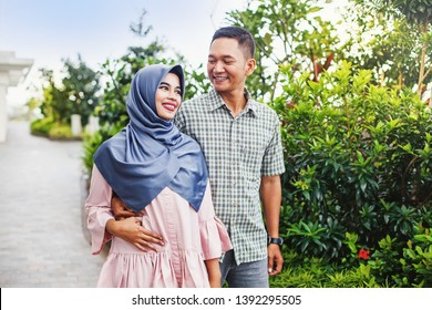Lovely muslim Indonesian couple walking in a park and talking