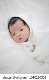 Lovely newborn Asian baby sleeping on furry cloth
