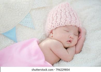 Lovely newborn Asian baby sleeping on furry blanket