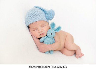 Lovely newborn baby boy hugging his plush toy
