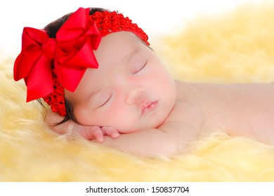 Lovely newborn baby girl sleeping on  yellow fur and white background, wearing a red ribbon.