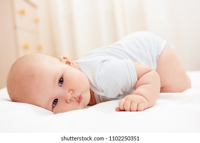 Lovely newborn baby lying on the bed in children's room.
