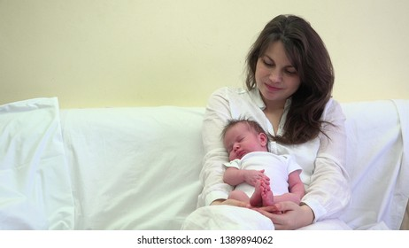 Lovely newborn baby sleeping in mother arms, happy attractive woman feel love
