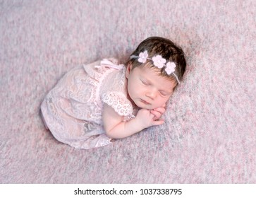 Lovely newborn girl in dress sleeping