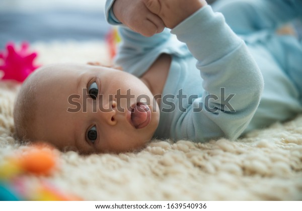 Lovely newborn kid lying on his back with hands up and showing his tongue