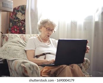 Encantadora anciana usando un portátil en casa.