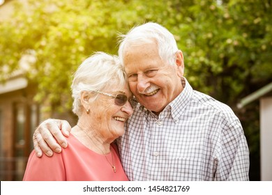 Lovely old senior couple smiling and have a romantic life together, they standing outside in the garden