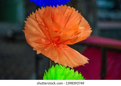 "Lovely orange paper flower, handcrafted by brazilian citizens during traditional june party (also named ""Sao Joao"" in portuguese speech). Closeup outdoor photograpy"