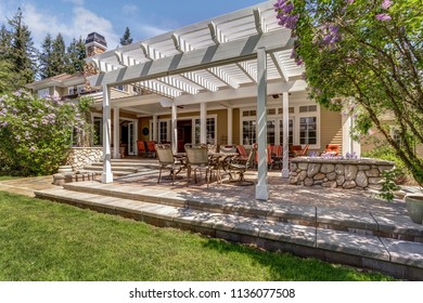 Lovely outdoor deck patio space with white dining pergola in the backyard of a luxury house.