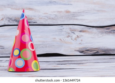 Lovely paper cone Birthday party hat. Patterned Bithday party cap on vintage wooden background with text space. Happy Birthday background.
