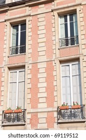 Lovely Paris windows of the pink brick buildings in the Place des Vosges of the Marais district.