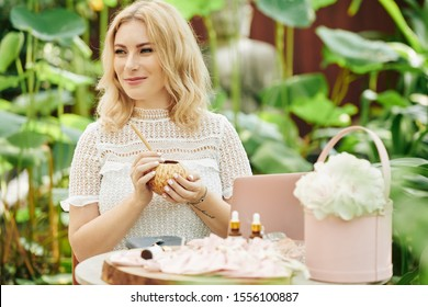Lovely pensive young woman enjoying sweet delicious coconut milk when sitting at table with cosmetics she created for online store