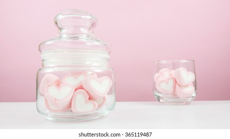 The lovely pink heart marshmallows in small glass jar and small round glass on white table for Valentine's day.
