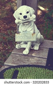 "a lovely plaster dog with ""Go away"" sign in a front door"