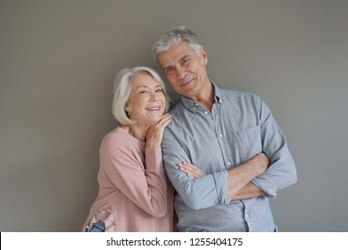 Lovely portrait of attractive senior couple on grey background