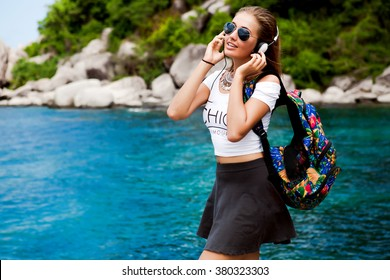 Lovely portrait of fresh beauty cute chick girl,hipster summer style outfit,aviator sunglasses,white big headphones,accessories casual,travel bag,fashionable street trendy outfit,summer vibe music