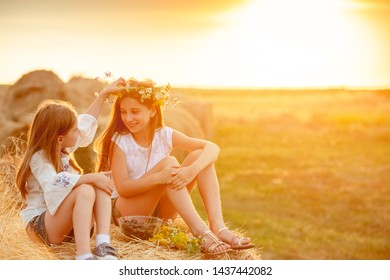 Lovely portrait of two caring sisters on background of summer dusk