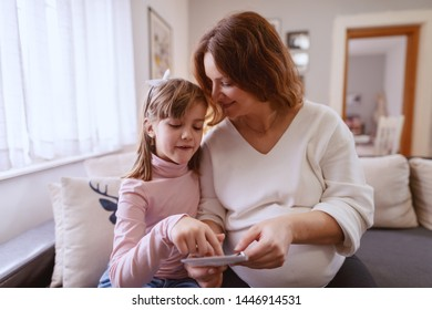 Lovely pregnant mom looking with her daughter ultrasound pictures of her unborn baby. Girl pointing at picture. Living room interior.