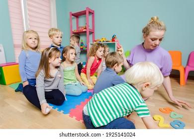 Lovely preschoolers listening young teacher very carefully
