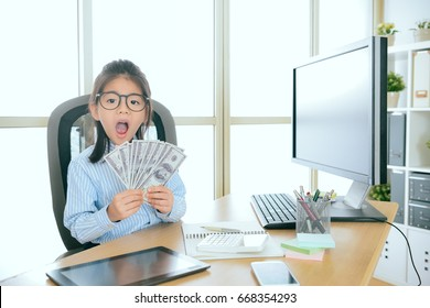 lovely pretty little girl kid children play as business people sitting on office desk and holding banknote showing accounting concept.