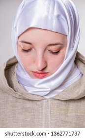 Lovely pure girl with eyes down in monastic clothes and white scarf