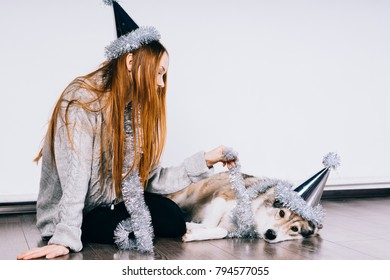 lovely red-haired girl with a cap on her head sits on the floor with her big dog, waiting for a new year and Christmas