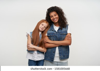 Lovely redhead long haired girl in jeans vest and white shirt leaning her head on shoulder of her curly dark skinned pretty friend female, looking at camera positively over white background