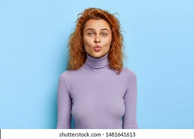 Lovely romantic feminine girl going to receive muah, keeps lips folded, waits for kiss, expresses love, wears purple turtleneck, has ginger wavy hair, pleasant appearance poses indoor has playful mood