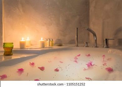 Lovely Romantic and Sexy Round bath full of foam, rose flowers, white wine and soft candle light ready to relax. Copy space for text area. Honeymoon concept for luxury hotel room.