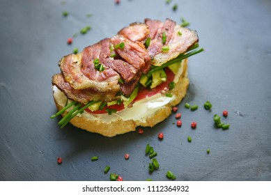 A lovely sandwich with bacon, avocado and onions on a dark slate tray.