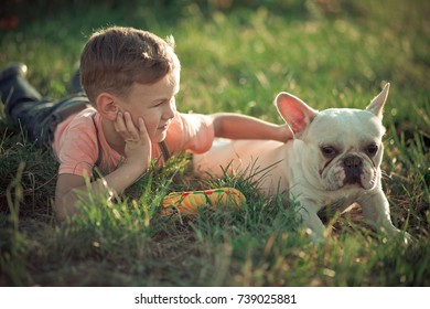 Lovely scene of friendship between handsome boy kid and bull dog doggy posing together in summer central park on green fresh grass wearing stylish clothes.